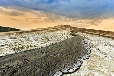 Mud volcano overflowing on bare mountain slope with cracked surface earth Stock Photo