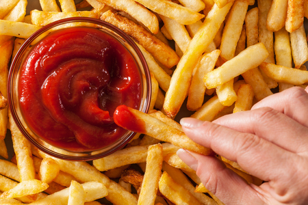 Hand dipping french fries in tomato sauce or ketchup - top view, closeup Stock Photo - 90025233