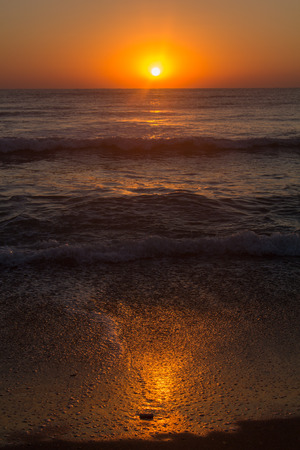 Sun setting over calm sea with waves braking on the orange hues shore