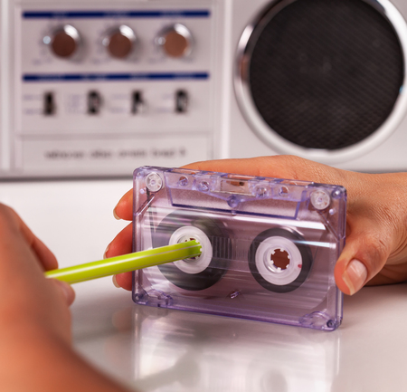 Woman reeling compact audio cassette by hand using a pen 版權商用圖片