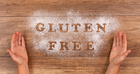 Hand presenting the gluten free alternative - diet choices and possibilities concept written in flour