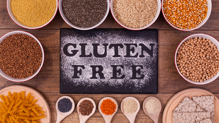 Gluten free diet options - various seeds and products around black plate with text written in flour, top view