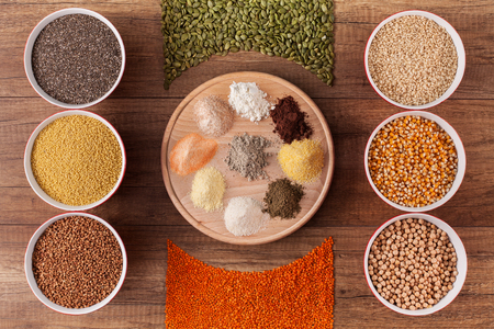 Various grains and seeds on the table and in bowls surrounding their corresponding flour in a colorful arrangement - top view