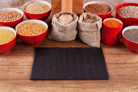 Various grains and seeds around a tabletop mill - whole food and diverse nutrition concept, copy space