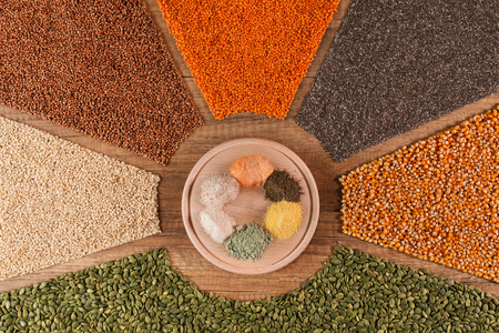 Various grains and their flour on a round plate in a colorful arrangement - top view 스톡 콘텐츠
