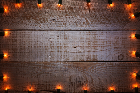Christmas decorative lights framing old battered wooden table - copy space