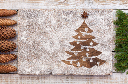 Seasonal and holidays decorations with copy space - christmas tree drawn in flour with pine branches and cones 스톡 콘텐츠