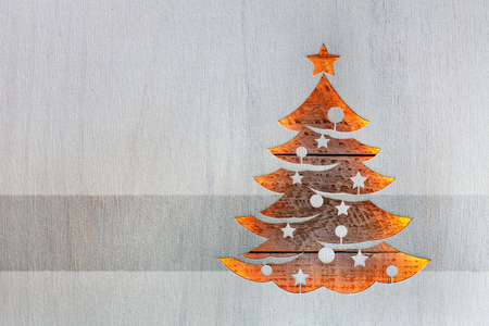 Christmas tree cut out from white painted wooden board letting warm ligths shine through - seasonal and holidays card, copy space 스톡 콘텐츠