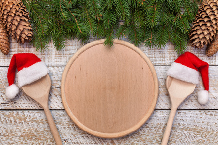 Christmas and holidays season menu with copy space on central round wooden plate and twoo spoons wearing santa hats