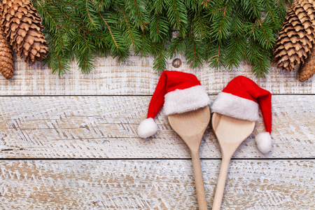 Planning the christmas menu - two wooden spoons wearing santa hats, with copy space