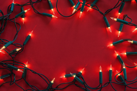 Old christmas decorative lights on red surface with dimmed shine - framing copy space in center