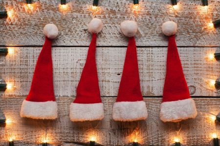 Small christmas hats on old wooden table with xmas lights frame - holidays season accessories