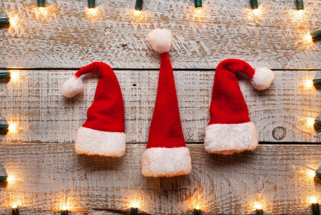 Christmas hats and decorative lights frame background - holidays season symbols, getting in the mood
