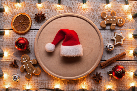 Preparing for christmas and the holiday season - with xmas decorations, cookies and ingredients on the table - santa hat in the center on wooden plate