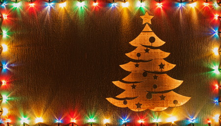 Christmas tree shape cut in wooden board lit from beneath surrounded with colorful xmas lights frame, copy space - holidays greeting design 免版税图像