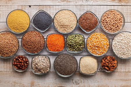 Varias semillas, granos y nueces en la mesa vieja, concepto de dieta diversa y saludable, vista superior Foto de archivo