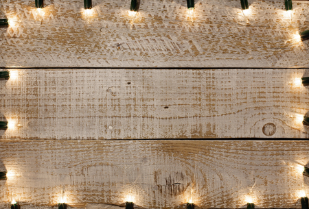 Copy space on white wooden planks with weathered paint - lit by small bulbs frame