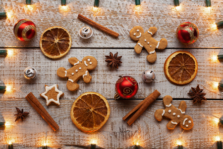 Christmas items background with xmas lights frame - holidays related decorations, cookies and spices 免版税图像