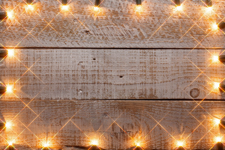 Generous copy space on old wooden planks with twinkling hazy lights frame - warm shades 免版税图像