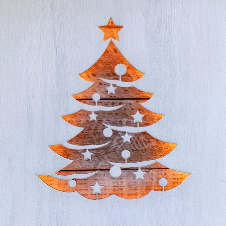 Christmas greeting with tree shape cut in wooden board revealing battered old surface and warm lights - traditional xmas concept