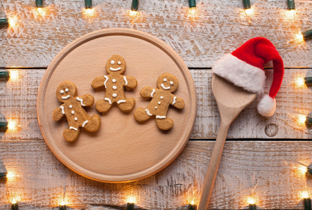 Christmas menu and recipe concept with cookies on wooden plate and spoon with santa hat - decorative lights frame