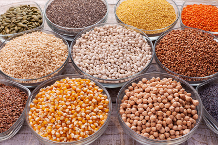 Various grains and seeds in glass bowls, diversified nutrition concept - closeup 免版税图像