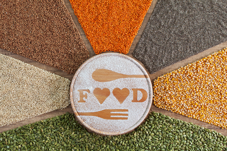 Love food concept with colorful variety of grains and seeds on brown table 스톡 콘텐츠