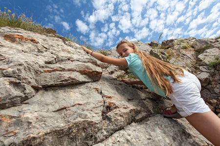 Young girl hiking in summer time - climbing up a rocky slope, looking down