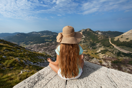 Girl on mountain top sitting and admire the view on a beautiful sunny summer day