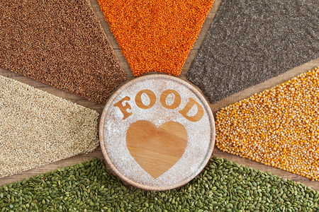 Love food concept - plant based food with diverse grains and seeds surrounding heart shape drawn in flour