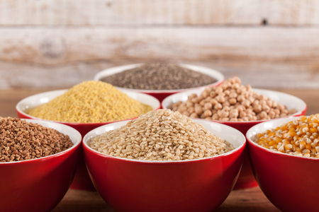 Various grains and cerelas in red bowls consisting of buckwheat, rice, corn, millet, chickpea and chia on wooden background - copy space 스톡 콘텐츠