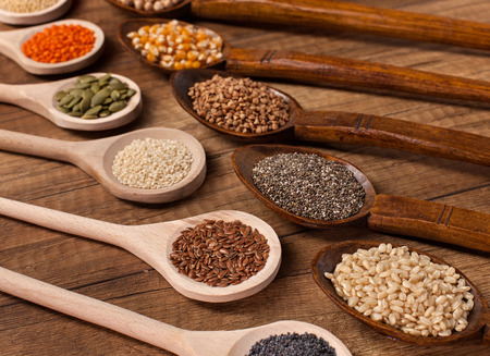 Various seeds and grains in wooden spoons - diversified plant based wholemeal diet concept 스톡 콘텐츠