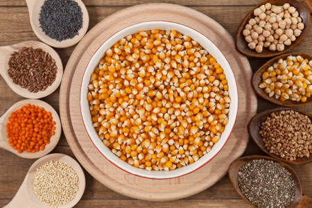 Grains and seeds variety - healthy and diverse food concept, with bowl of corn in the center