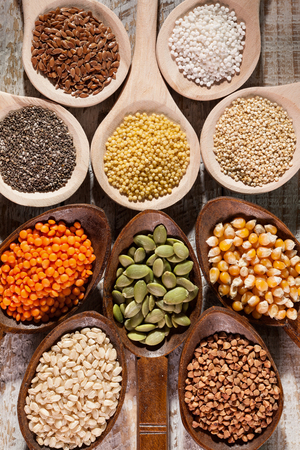 Various colorful seeds and grains for the gluten free diet - wooden spoons close up, top view. Diverse staple food for healthy eating.