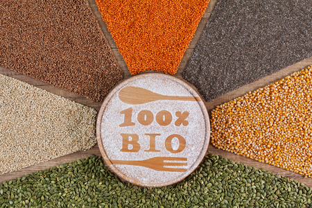 Bio and organic food concept - with colorful whole grains and seeds in radial arrangement consisting of buckwheat, lentils, chia, corn, pumpkin seed and rice