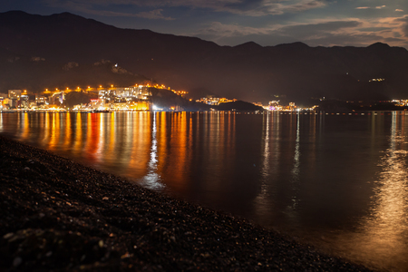 Seaside resort at night in summer with mountains nearby and the moon lighting the sky