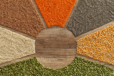 Colorful grains and seeds background with copy space - healthy whole food choices. Variety of nutritious staple food