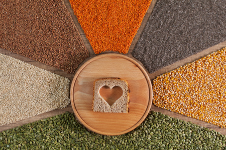 Healthy whole food diet choices - with colorful grains and seeds in radfial arrangement. Bread slice with heart shaped hole in center