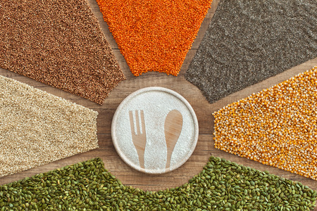 Eating a healthy and diverse diet concept - colorful grains, seeds and cereals surrounding round board with fork and spoon shape drawn in flour