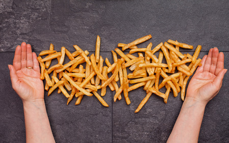 Woman hands serving and presenting french fries on slate table - top view