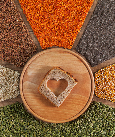 Food with love. Heart shaped hole in bread slice surrounded by colorful grains and seeds.