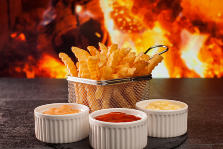 Delicious french fries meal with various sauces - in front of fireplace, on dark slate table