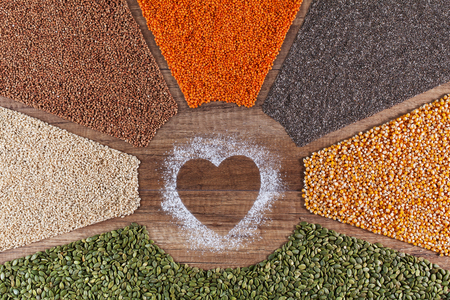 Food with love - plant based diversified diet concept with colorful grains and seeds surrounding heart shape drawing in flour