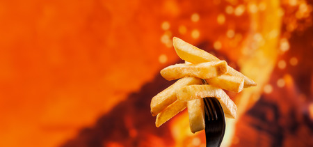 Delicious french fries on a fork - fire background with copy space, close up 免版税图像 - 122944582