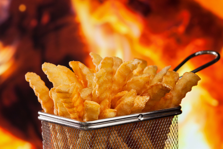 Delicious french fries in frying basket serving recipient on fire background - close up