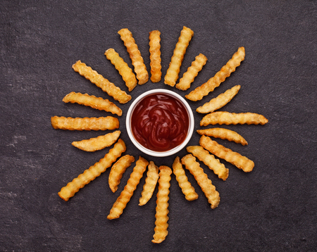 French fries and ketchup arranged in the form of flower petals on dark slate background - top view