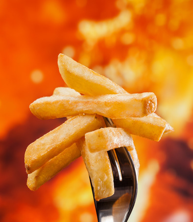 Delicious french fries stuck on fork - fire background, close up 스톡 콘텐츠