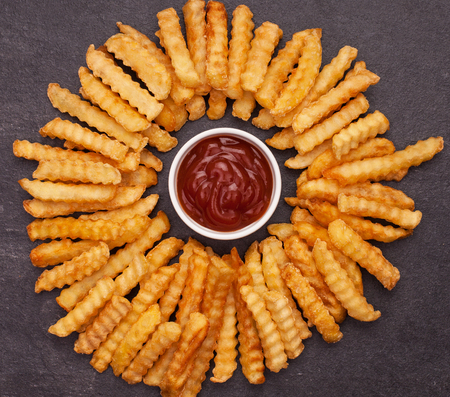 Fries arranged in a circle around ketchup bowl on dark slate background - top view