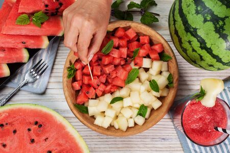 Watermelon bites on a plate with melon slices, half melon and red smoothie around. Hand picking a healthy summer snack, top view