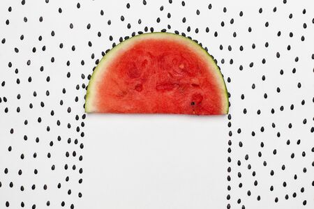 Watermelon seeds raining on melon slice protecting the area beneath as an umbrella - on white background with copy space 免版税图像 - 130393336